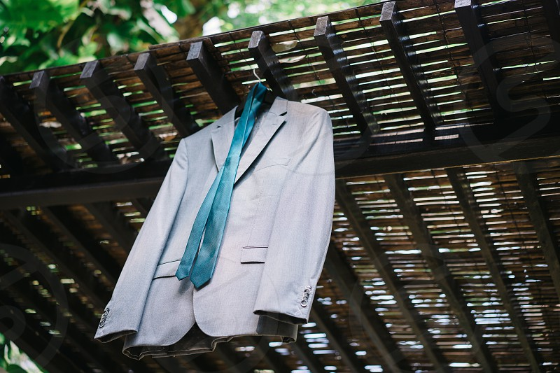 The groom suit with teal neck tie hanging outside photo