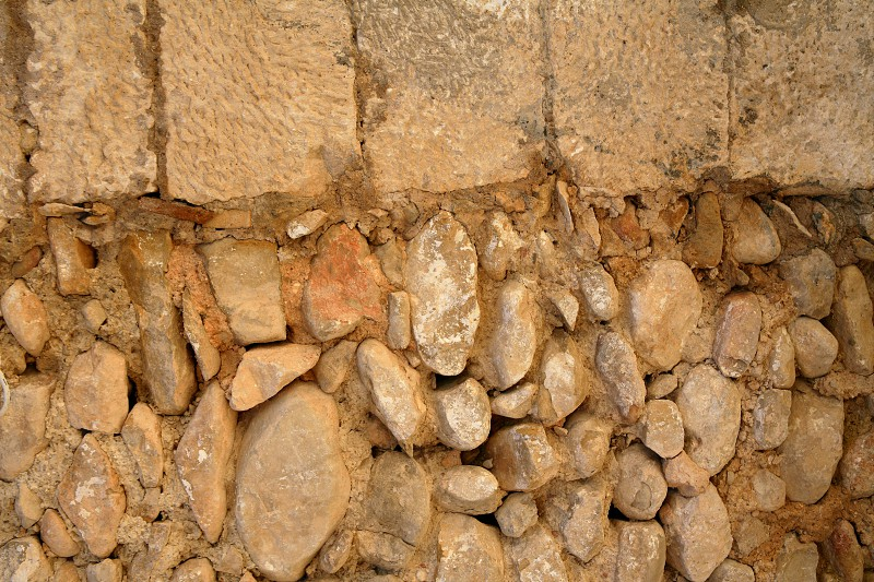 Golden masonry stone wall from old building contruction facade photo