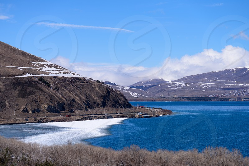 Lake Sevan in Armenia on early April sunny day with lake partly covered with ice.  photo