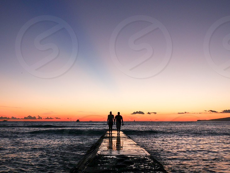 Couple silhouette holding hand walking on a pier into the ocean at golden hour vacation Valentine's Day  Love romantic  photo