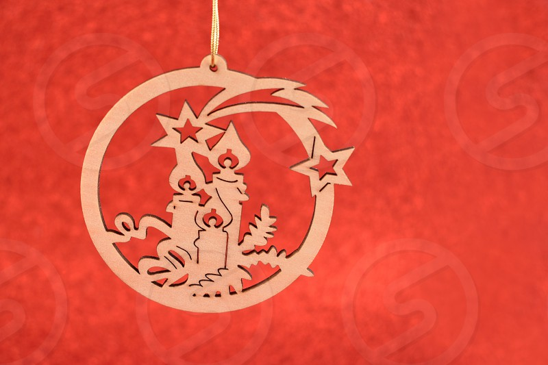 Carved Christmas decoration. Carved wooden ornament. Christmas decoration on a red background. Holiday background with copy space for text photo