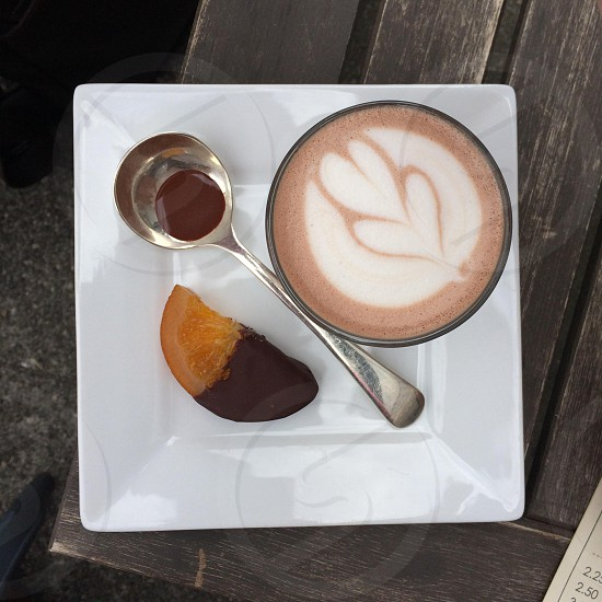 black ceramic coffee mug with stainless steel spoon on top of square white ceramic plate photo