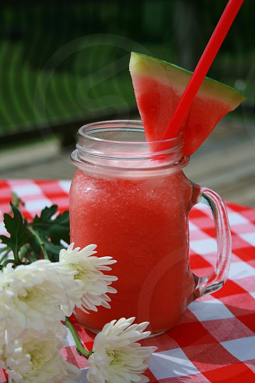 Refreshing Watermelon beverage drink summer flowers checkered tablecloth table deck outdoors photo