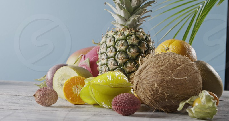 Fresh pineapple coconut carambola and fresh tropical fruits on a gray wooden table on a light blue background. Panoramic motion 4K UHD video 3840 2160p. photo