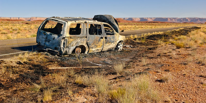 The burned out shell of a vehicle along US Highway 163 just north of Mexican Hat in Utah. This road leads to the Valley of the Gods. Nobody was hurt during this fire but if the people were on their way to visit the Valley of the Gods they were out of luck for this trip. photo