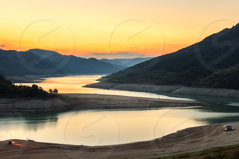 Amazing view of curvy meandering Zavoj lake on Old mountain at golden hour during minimal water level  photo
