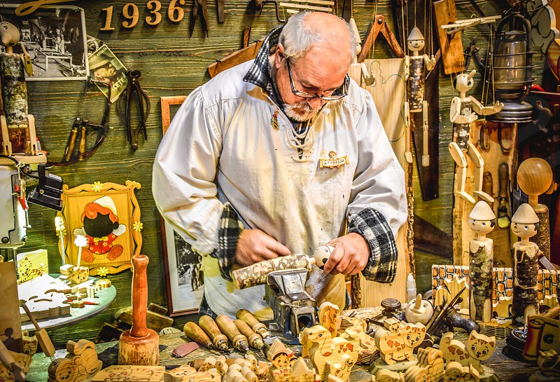 A Craftsman Working In The Workshop Making Wooden Toys photo