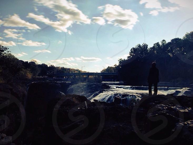 man standing near the waterfalls photo