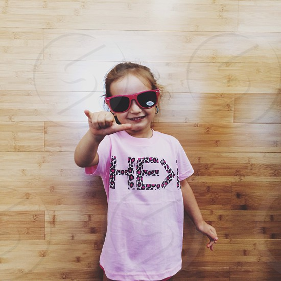girl wearing pink rimmed wayfarer sunglasses standing showing hang loose sign photo