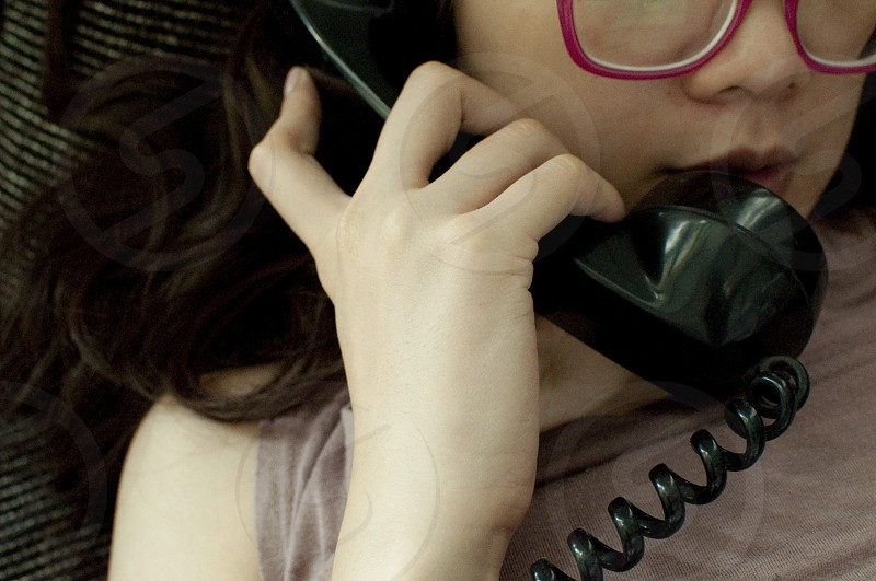 A woman calling with black vintage telephone photo