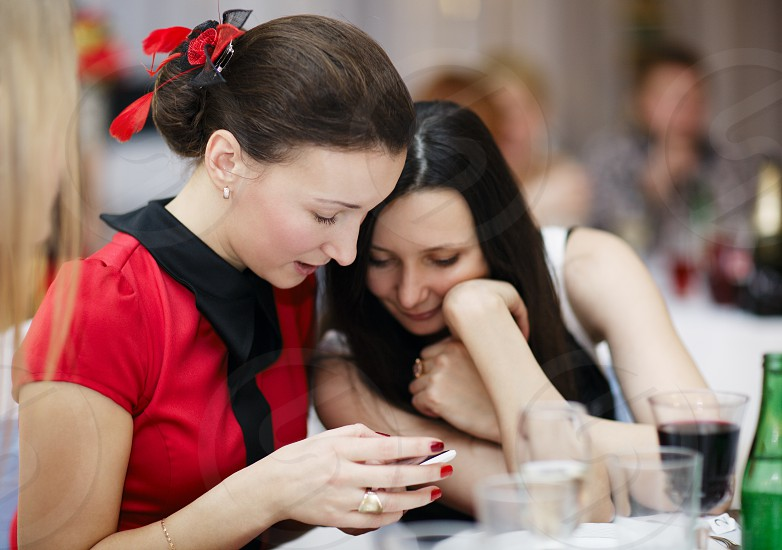 Two beautiful stylish young women at a formal event sitting together at a table reading an sms on a mobile phone photo