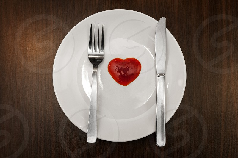 dishware fork knife ketchup white plate love sign heart sign heart shape concept top view cutlery dining tableware kitchenware utensils objects brown wooden table eating utensils nobody horizontal no people photo