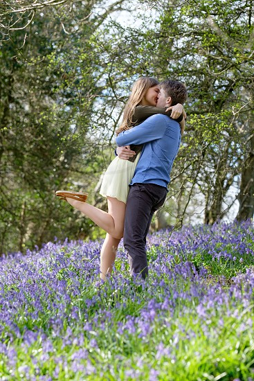 romantic couple cuddling kissing in the woods in the spring  with purple coloured blue bell flowers she is lifting one leg she is wearing a yellow dress and brown cardiganhe is wearing a blue shirt and grey trousers. The photo is taken in a portrait composition with copy space around the couple. photo