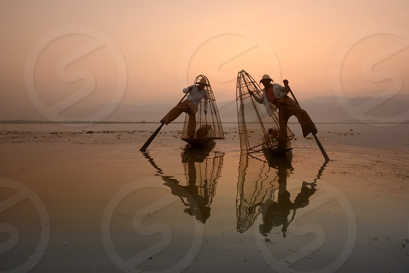 Fishermen at sunrise in the Landscape on the Inle Lake in the Shan State in the east of Myanmar in Southeastasia. photo