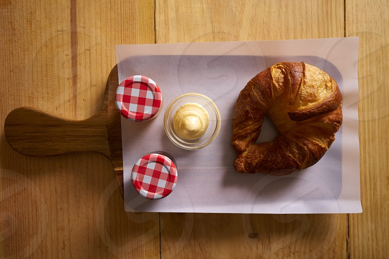 Breakfast croissant with butter and jam on wood board photo