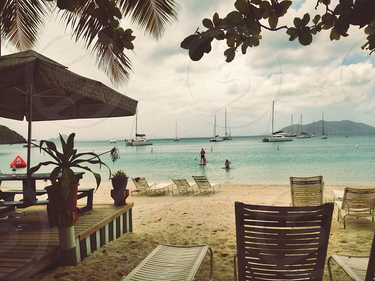 person paddle boarding in bat near beach with lounge chairs photo
