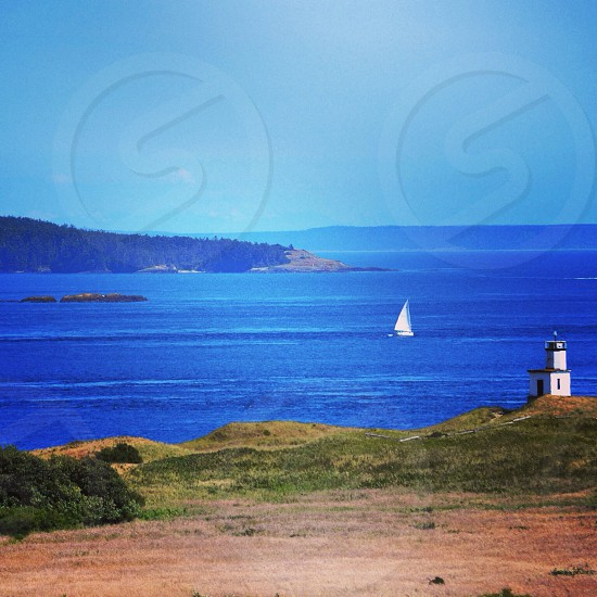 sailboat on body of water in front of lighthouse photo