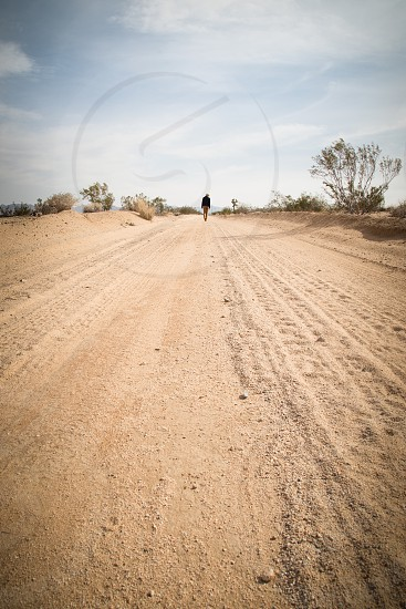 long desert dirt road with small figure in the distance photo