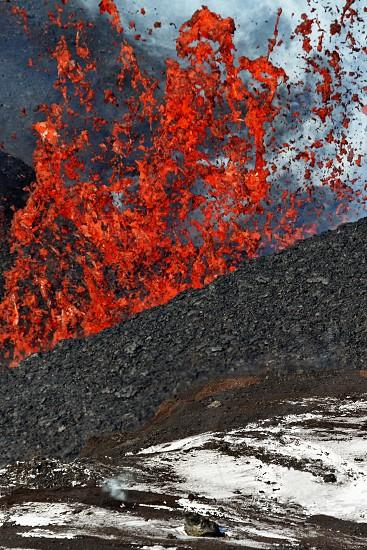 Natural hazard landscape: beautiful eruption volcano on Kamchatka Peninsula - red hot lava fountain erupting from crater active Tolbachik Volcano. Russian Far East Klyuchevskaya Group of Volcanoes. photo
