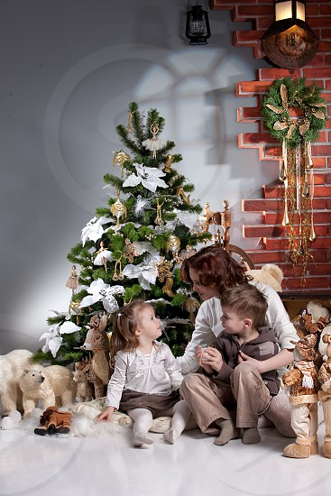 toddler girl and boy sitting with mom at the christmas tree with polar bears and deer photo