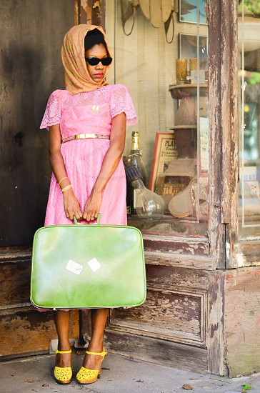 woman in pink dress carrying a green luggage photo