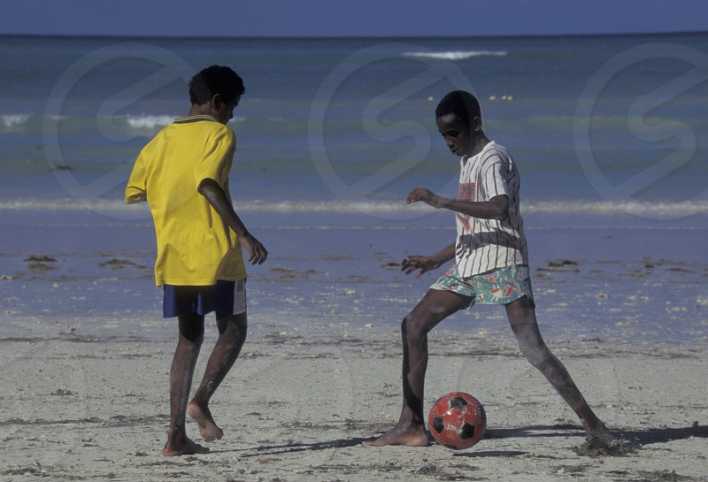 boys play soccer on a Beach on the coast if the Island Mahe of the seychelles islands in the indian ocean photo