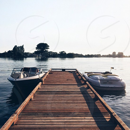 white speed boat beside dock photo