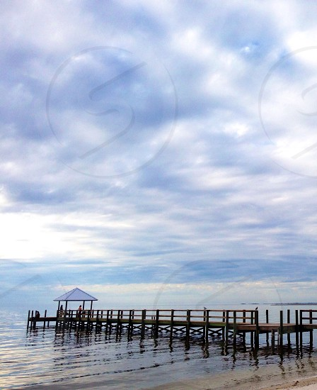 wooden pier and water with white clouds photo