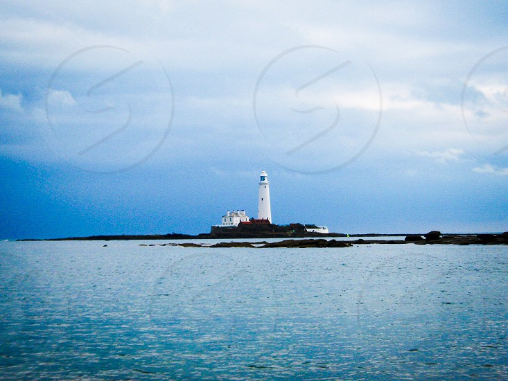 White lighthouse over blue sky and blue sea photo