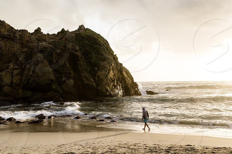 person on the beach next to large rock photo