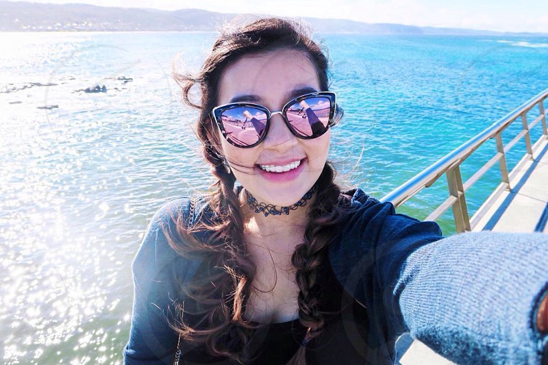 woman in black framed purple and pink 2 toned cat eye sunglasses with black tattoo choker near in the shore during sunny day photo