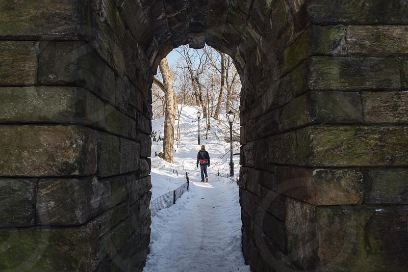 man walking through bricked arch tunnel photo