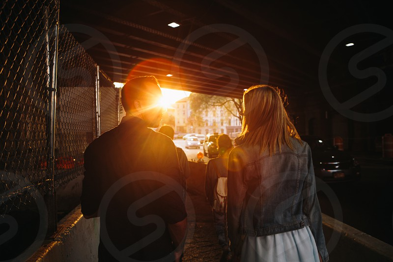 yellow sunlight rays through woman in blue denim jacket and white skirt walking beside man in black dress shirt photo