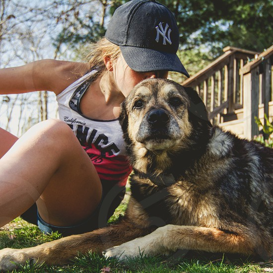 woman in white and black tank top sitting on grass field with medium short-coated tan dog on selective focus photography photo