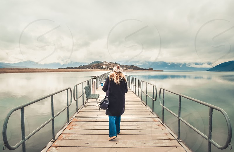 Wanderlust Young Woman Walking On Bridge Toward The Island photo