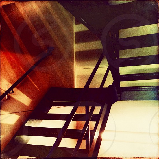 the belly of the behind the scenes. fire escape stairs shadows light red blue photo