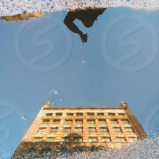 puddle in street reflecting brown building exterior photo