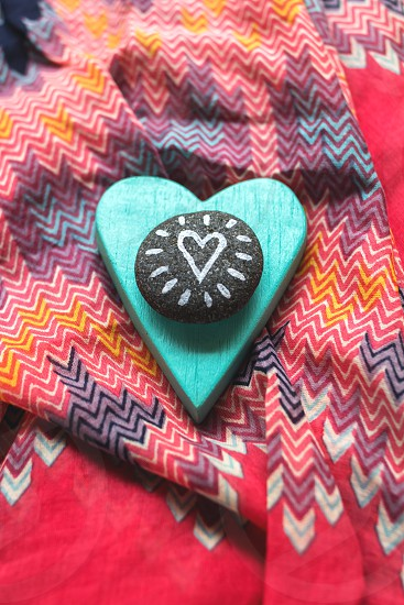 little stone with picture of heart and painted wooden heart on colorful fabric photo