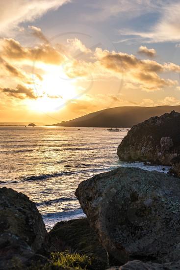 Sun sunset rocks cliff cove pirates pirates cove beach ocean sea sand water waves salt boat pier dock photo