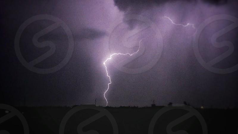 lightning striking ground under cloudy sky photo