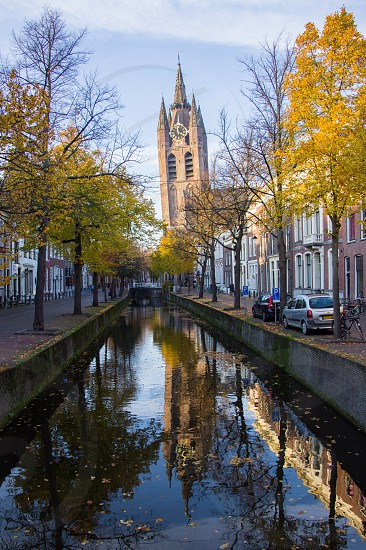 A side street with canal in Delft Netherlands.  The Old Church has a leaning tower. photo