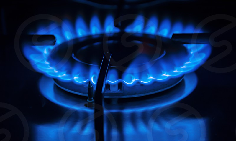 Blue flame of the stove in the kitchen. Gas and energy concept. photo