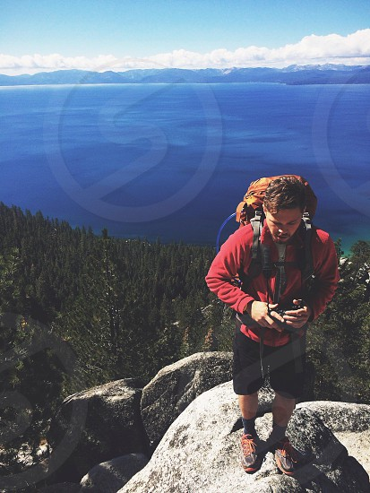man in daypack in rock photograph  photo