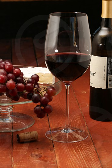 glass of red wine with grapes and cheese and bottle photo