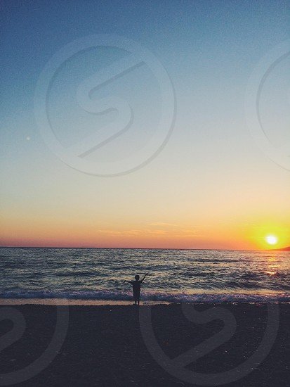 boy standing near sea at sunset view photo