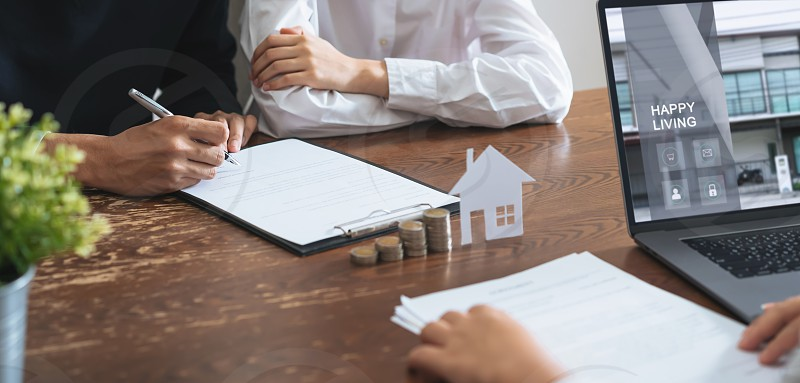 Couples signed a contract to buy a house from the broker. Coin to stack money and model house placed on the table financial Business Growth. photo