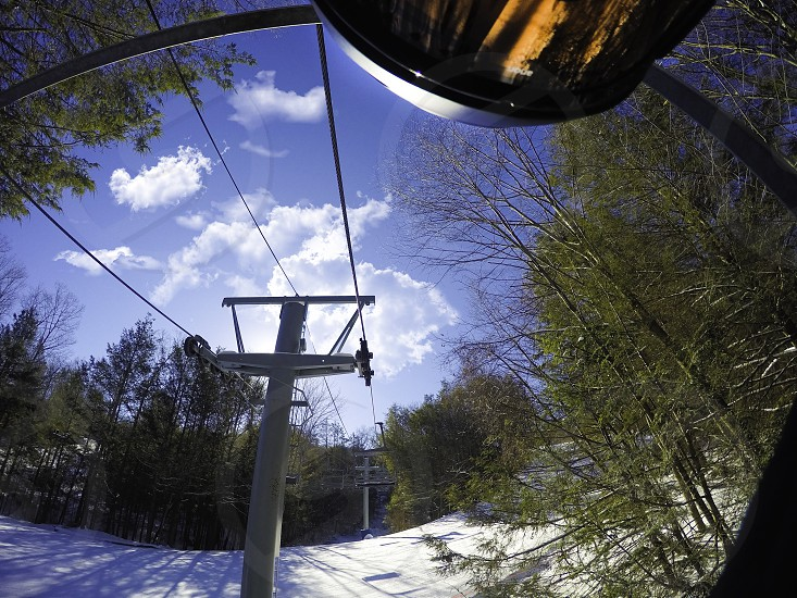 grey metal ski lift on white snow covered mountain side by green trees under blue sky with white clouds photo