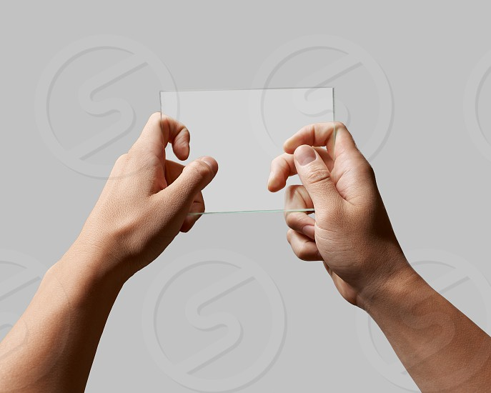 rectangular transparent glass in male hands on a gray background place for text photo