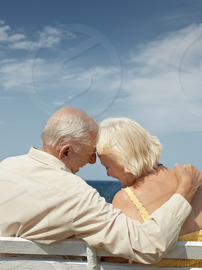 Old retired senior couple sitting on bench at the sea and hugging. Copy space photo