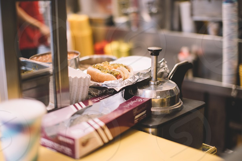 selective focus photo of 2 hotdog sandwich on white plate on table beside sauce dispenser and red purple and white label box photo